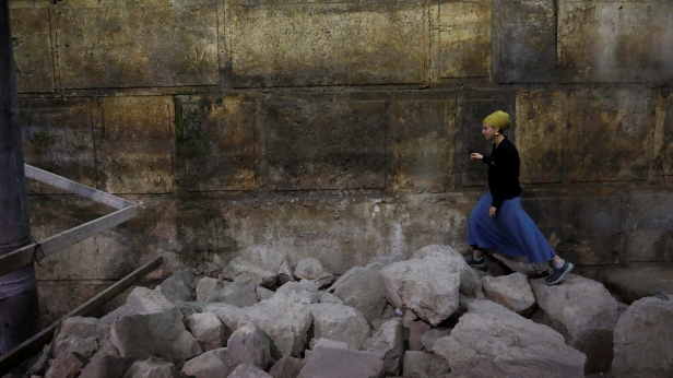 Israel Antiquities Authority archaeologist Tehillah Lieberman walks atop stones lying besides a part of the Western Wall, during a media tour revealing a theatre-like structure in Jerusalem's Old City