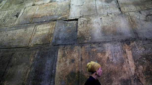 Israel Antiquities Authority archaeologist Tehillah Lieberman stands next to a part of the Western Wall, during a media tour revealing a theatre-like structure which was discovered during excavation works underneath Wilson's Arch, in Jerusalem's Old City